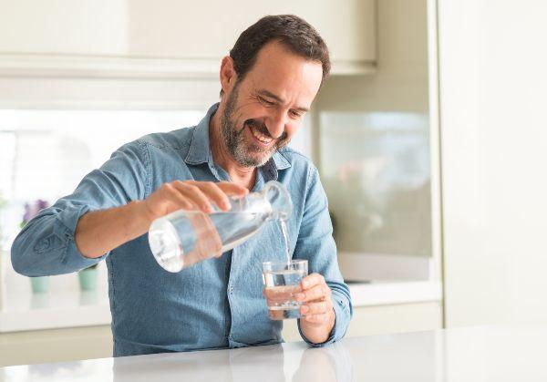 privlačen starejši moški pije vodo, da bi preprečil suhe oči ponoči