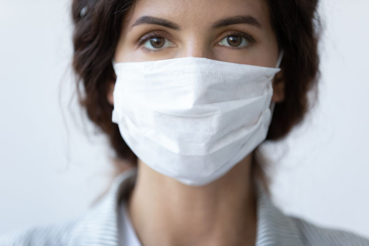 zaščitna maska na lepotici, ki ima zaradi tega suhe oči in rabi kapljice za oči